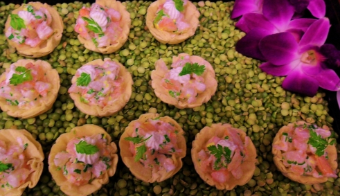 Shrimp in Phyllo displayed on tray filled with dried split peas and flowers